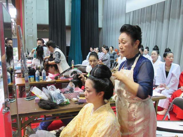 琉装の女性の髪を結う知念さんの写真