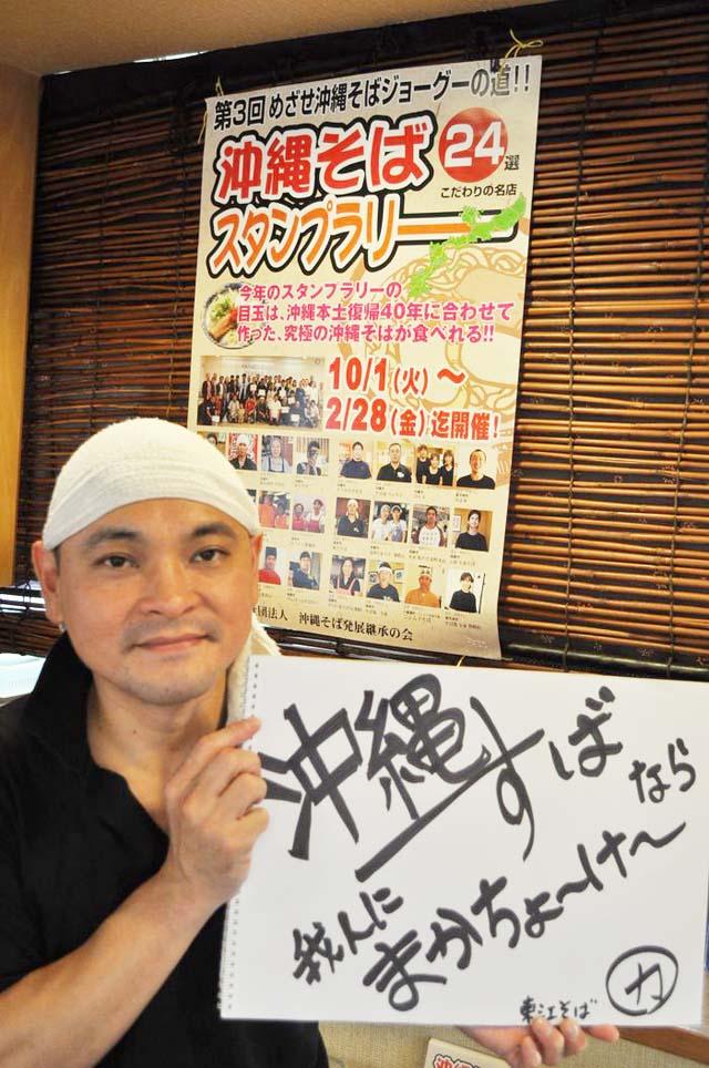 「沖縄そばスタンプラリー」のポスターの前でポーズを取る屋比久さん